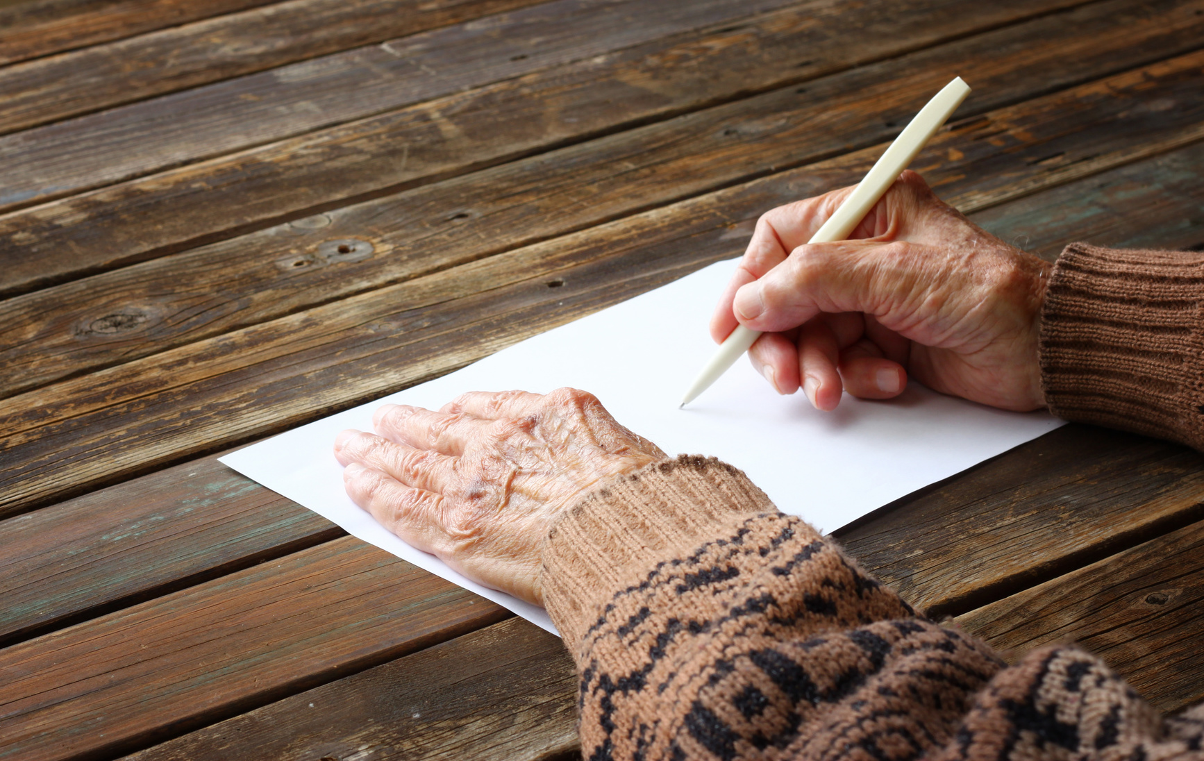 close up of elderly male hands on wooden table